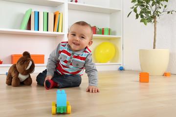 Lachendes Baby Kind beim Spielen mit Spielzeug