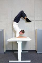 flexible business man in scorpion asana on desk in his office