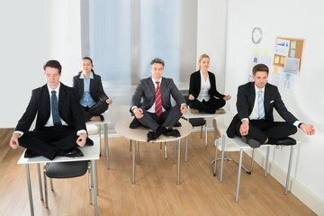 Meditating Businesspeople Sitting On Desk