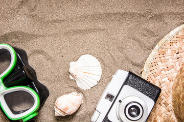 summer hat, snorkel, shell and old camera on sand
