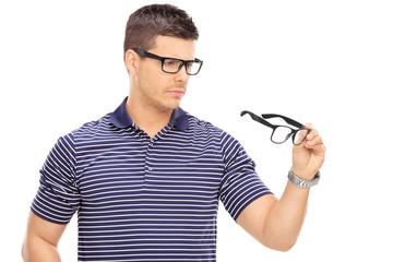 Man looking at a pair of glasses
