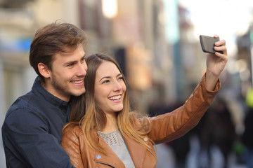 Couple taking selfie photo with a smart phone in the street