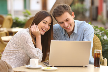 Couple watching media in a laptop in a restaurant