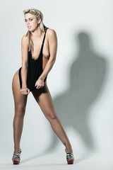 Slim topless young woman pulling the dress