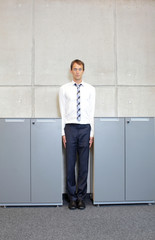 white business man standng straight between cabinets in office