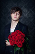 Young handsome man with a bouquet of a red roses.