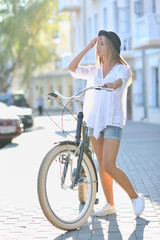 Full length portrait of a beautiful girl with bicycle