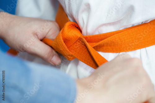 Foto op Canvas Vechtsport Father ties an orange belt on his son's martial arts uniform