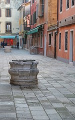 ancient marble well in calle of Venice
