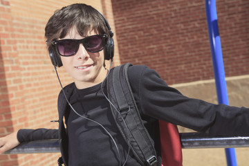 A teen boy listening to music with sun glasses