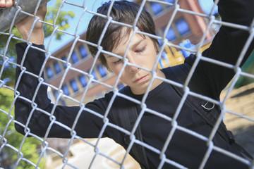 A sad boy on a school playground closing