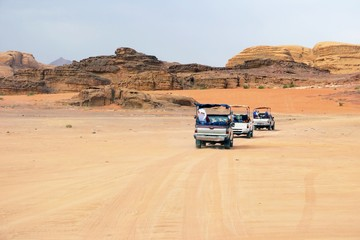 cars of tourists in search of adventures in the desert