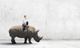 Man saddling rhino