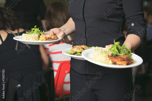 A Young waitress with plate on his hand - 78107182