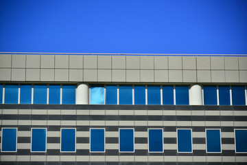 Building facade in concrete and glass in blue