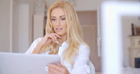 Pretty Blond Woman Looking at her Laptop Seriously