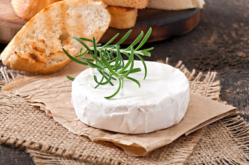 Camembert cheese and a sprig of rosemary on a wooden table