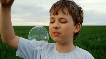 boy blow bubbles outdoors