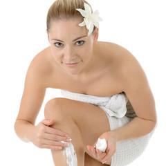 Frau cremt Beine ein