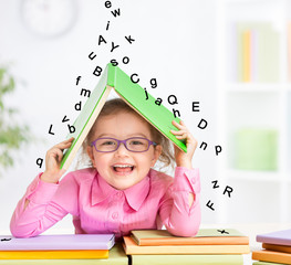 Smart smiling kid in glasses taking refuge under book roof from