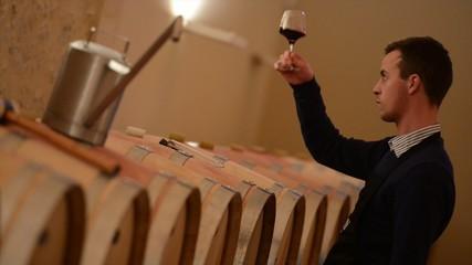 Winemaker tasting wine amongst oak casks.