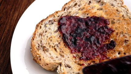 Spreading blueberry jam on whole wheat toast in slow motion