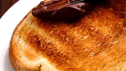 Spreading smooth hazelnut chocolate spread on toasted bread