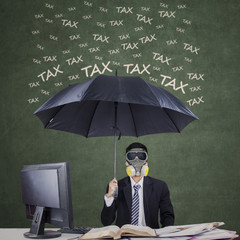 Entrepreneur with umbrella to protect from tax
