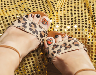 photo of pedicure like butterfly design on gold background close