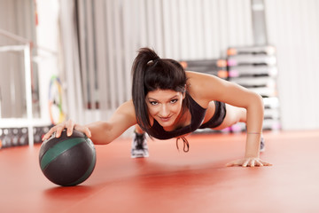 pretty young woman doing pilates exercises with a medicine ball