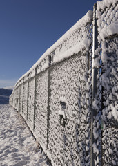 Chain-link fence line covered in snow with blue sky