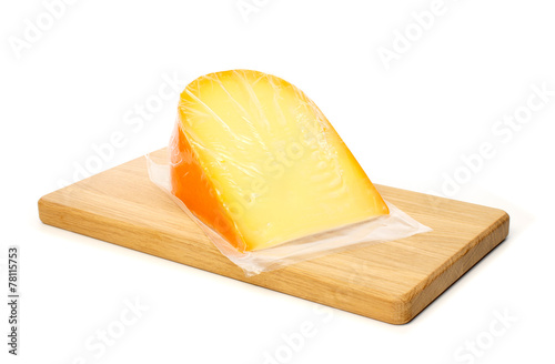 Staande foto Zuivelproducten Cheese in vacuum packing on cutting board