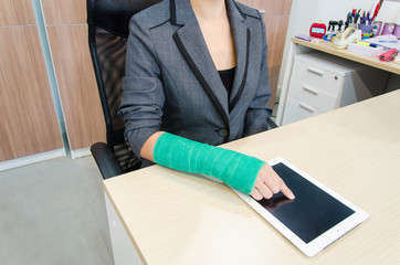 Injured businesswoman with broken hand  and green cast on the wr