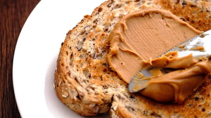 Peanut butter being spread on whole wheat toast