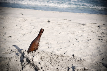 bottle of beer stuck in the sand