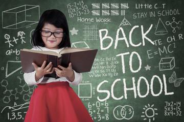 Girl read a book in front of blackboard