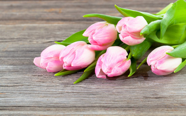 Bouquet of pink tulips on old wooden boards