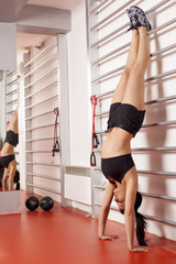 pretty young woman doing a handstand next to bars