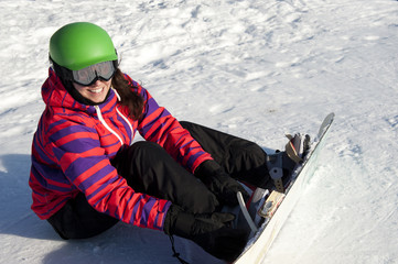 young woman putting on a snowboard