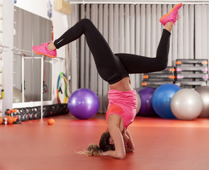 pretty young woman doing pilates handstands