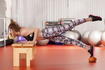 pretty young woman doing push-ups on the bench and medicine ball