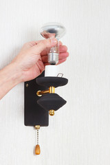 Hand unscrews incandescent lightbulb in a lamp on a white wall