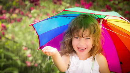 Happy child walking in the rain. Funny kid with bright multicolo