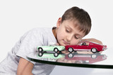 Boy playing with two toy cars