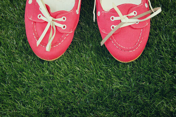 top view of red worn woman shoes over grass textured background