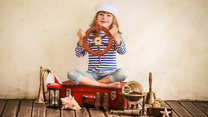 Happy kid playing with nautical vintage toys. Slow motion