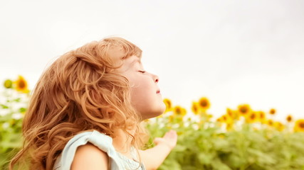 Happy child enjoying in spring sunflower field. Slow motion