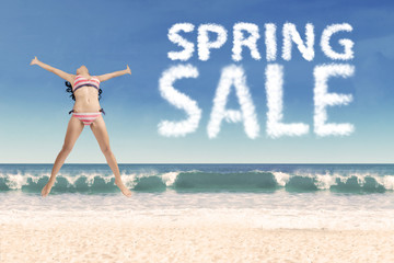 Sexy girl on beach with spring sale text
