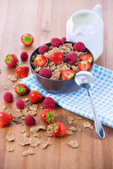 Bran flakes with fresh raspberries and strawberries and pitcher