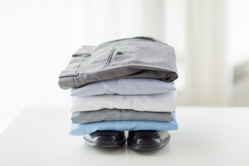 close up of male shirts, pants and shoes on table